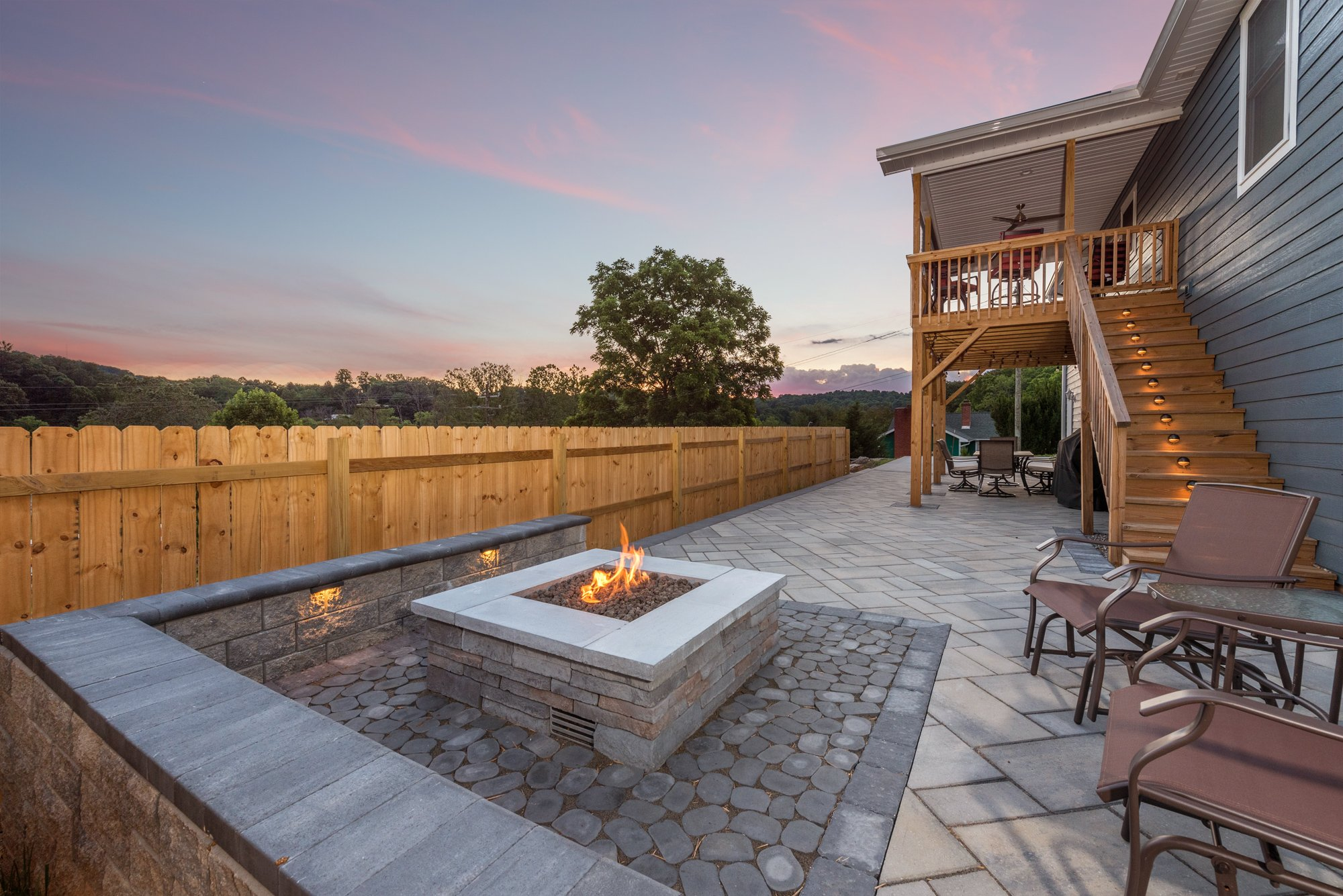 Premier paver patio installation including: new fence installation, thorough outdoor lighting, wrap-around outdoor seating, and more, in Asheville, NC