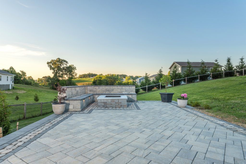 A custom patio paver installation including wrap around, built-in seating, and a custom fire pit in Leicester, NC